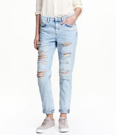 Light denim blue. 5-pocket, low-rise jeans in washed denim with heavily distressed details, button fly, and slightly wider, tapered legs.