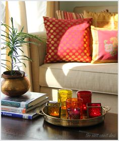 a collection of tea light holders in warm hues placed on a vintage brass tray