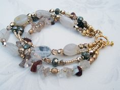 Boho natural quartz and gold beaded. This earthy boho multi-strand was handcrafted from natural rutilated quartz chips varying in color clear, beige to taupe paired with clearish-white quartz oval beads, gold (both matte and shimmery) Czech fire-polished beads, Czech metallic gold seed beads and faceted pyrite rondelle beads. The 4 strand bracelet is clasped with a gold plated toggle. Mixture of neutral colors in shades of light taupes and browns mixed with the clear and gold beads.