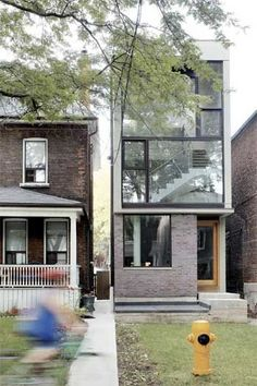unusually narrow lot combined with strict building restrictions,  the Galley House in Toronto's Roncesvalles neighborhood; this 12-foot-wide  2,100 sq. ft. three-story detached house with a modern composition of glass panes and purple brick.