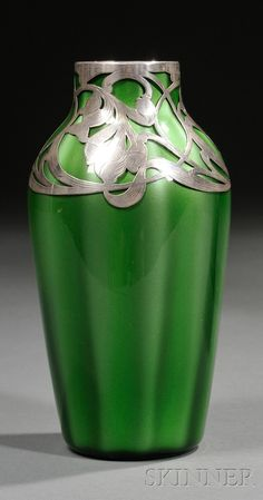 Loetz Metallin Art Glass Vase with Silver Overlay   Art glass and silver   Austria, 1905-1920   Green paperweight style ribbed ovoid form with silver floral decoration at neck and shoulder, ht. 6 1/2 in.     Note: This Art Nouveau metallin vase is the earlier version of the later developed Titania series by Leopold Bauer.
