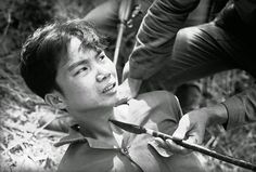 With the persuasion of a Viet Cong-made spear pressed against his throat, a captured Viet Cong guerrilla decided to talk to interrogators, telling them of a cache of Chinese grenades on March 28, 1965. He was captured with 13 other guerrillas and 17 suspects when two South Vietnamese battalions overran a Viet Cong camp about 15 miles southwest of Da Nang air force base. (Eddie Adams/AP) ~ Vietnam War