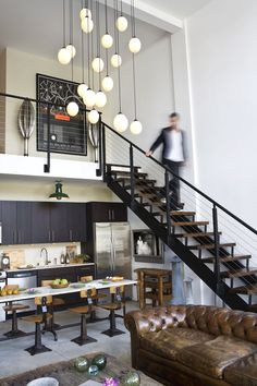 modern loft living* love the worn leather chesterfield* contrast of cabinetry and white* lovely loft*