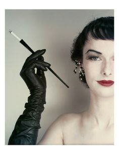 Vogue - October 1952 - Woman with Cigarette Holder / Model Victoria von Hagen wearing jet and glitter earrings, full-length gloves by Superb. / by Erwin Blumenfeld