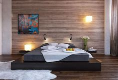 Black platform bed with wood clad bedroom wall