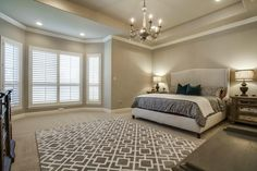 Elegant white and gray master bedroom // Tray ceiling, bay window with plantation shutters