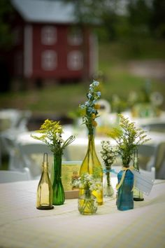 I love the idea of little green and purple glass bottles in all different shapes and sizes holding small flower bouquets on each of the tables at the reception.