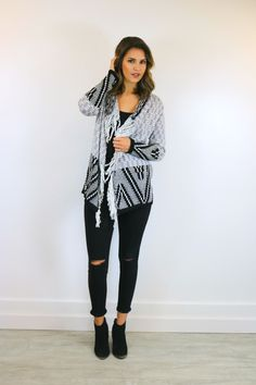 This double breasted knit cardigan sweater is the perfect piece to get you ready for the colder weather. With a geometric print in black, white and gray with fringe hem this sweater pairs perfectly wi