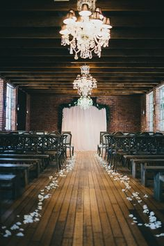 Chandeliers killing it by contrasting with the industrial details and rustic wood floor.  (carondelet house wedding)