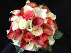 Hand tied bouquet created with ivory roses, Sahara roses, ivory mini calla lilies, coral roses and Mozart mini calla lilies.