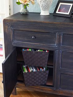 For a family of six, closed-door storage to hide clutter is a must. Two durable plastic cubbies corral DVDs in the new dark-stained poplar media console. With movie titles easily visible, they're grab-and-go convenient.