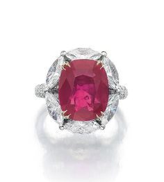 RUBY AND DIAMOND RING. The cushion-shaped ruby weighing 8.21 carats, set within a frame of marquise-shaped diamonds, the shoulders pavé-set with brilliant-cut diamonds