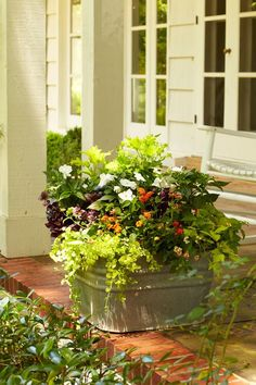 Rustic Freestanding Container - Front Door Container Gardens That Will Impress Guests - Southernliving. Trash is turned into beautiful treasure with this budget-friendly, galvanized-metal washtub container. Maroon Joseph's coat, green coleus, and yellow creeping Jenny accents the front porch or entryway.