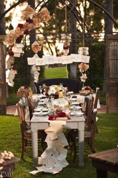 """7 books are suspended above table """"when I saw you I fell in love & you smiled because you knew"""" written on the books. Pages of Books are folded or created into large flowers, and table runner. Stacks of vintage books around other areas.This is a Rehearsal Dinner"""