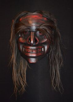 "Beau DIck - Bookwus Mask - - Red cedar, acrylic paint, leather, horsehair -     25"" x 26.5"" x 16""   Bookwus (Wild Man of the Woods) is a supernatural being who lurks on the edges of forests and near streams trying to lure living people into his invisible abode."