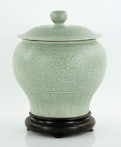 "Celadon jar on wood stand, with cover, incised floral design, lotus blossom handle on cover, China, Ming dynasty style, 11"" h x 9 1/2"" w, 13"" h overall."