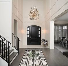 Beautiful entrance hall, entryway, foyer, black door. Wooden flooring and stair treads