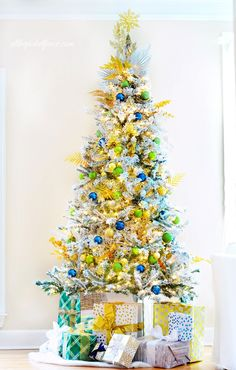 A fresh take on traditional Christmas decorating! Flocked tree with gold, green and blue ornaments and mirrored tree stand!