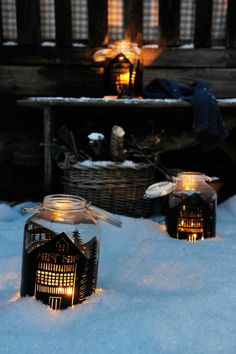 christmas mason jars, two jars with little houses painted on them in black, containing lit candles, and placed on snow near a house