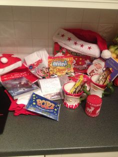 Contents of Christmas Eve box - Christmas book, pjs, Christmas hats, DVD, candle, reindeer dust, cups with hot choc, marshmallows and flake, sweets, candy canes, popcorn and a Christmas craft set