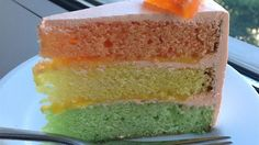This tri-colored cake has a lemon layer, lime layer, and an orange layer. The filling is a lemon curd and the frosting is orange.