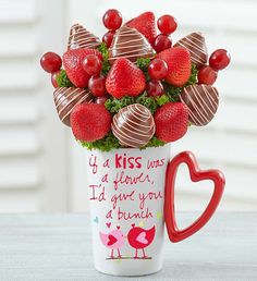 """Mugable® Bunch of Berries """"If a kiss was a flower, I'd give you a bunch!"""" That's the sentiment behind this bunch of delectable strawberries—some dipped, some plain, all plump—bursting from a keepsake mug designed by inspirational artist Sandra Magsamen. With a charming design and heart-shaped handle, it's a sweet gift from one lovebird to another."""