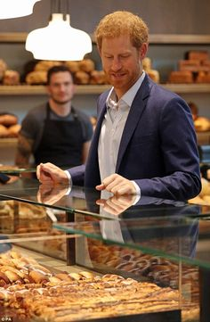 Prince Harry looks at pastries at a bakery in Hellerup, Copenhagen, during his official visit to Denmark
