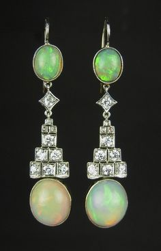 White gold opal and diamond drop earrings, test 18 ct. White gold opal and diamond drop earrings, test 18 ct. Each set with two oval water opal cabochons, seven round brilliant cut diamonds and three rose cut diamonds. Opals show a pleasant green, orange and yellow play of colour.