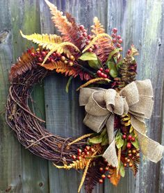 Autumn grapevine wreath with fall-colored Boston Fern, seasonal berries, and a burlap ribbon via Etsy