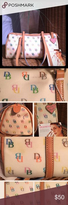 NWT Dooney & Bourke It Barrel Bag Brand NEW It Barrel Bag in White w/Multi-Color DB's. Never been used, so no scratches on the leather trim & no wear on the handles. Light scuffs on the white coated material that weren't noticed when it was purchased at Macy's & an ink mark on the end. I haven't tried to remove any of these marks, bc I prefer a bigger bag. I'd think since it's coated, they'd come off. Also some slight discoloration on the bottom of the bag. Please feel free to ask…