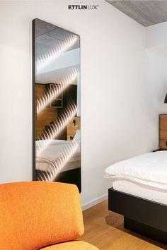 Ambiloom® Mirror 1700 ist ein moderner Ganzkörperspiegel mit ambienter Beleuchtung. Aus der Verschmelzung von Licht und Textil entstehen unvergleichliche Lichteffekte in der Spiegelung. Das verleiht dem Design Spiegel weitaus mehr als elegante Funktionalität. Er ist ein Stück Wandkunst, das die Wahrnehmung der Hotelgäste weckt. Sein Lichteffekt durchbricht starre Hotelzimmer und verleiht optische Tiefe. #ambiloom #ettlinlux #spiegel #lichtspiegel #hotel #hotelzimmer #hoteldesign #lichtdesign Blinds, Curtains, Mirror, Home Decor, Hotel Bedrooms, Indirect Lighting, Light Design, Modern Full Length Mirrors, Interior