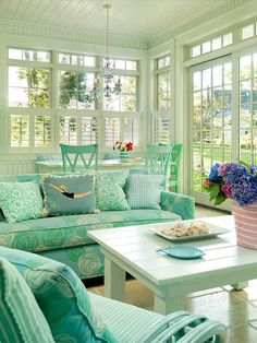 If I ever have an enclosed porch, I want it to look like this. How pretty! You could even buy a table at a garage sale and paint it like that.