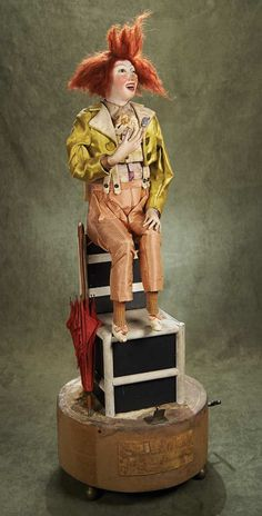 Rare French Musical Automaton.When wound,his eyelids blink rapidly and alternately,as though winking,while he lifts the pastry to his mouth; his tongue flits in and out rapidly as though licking the sugar on the pastry,while his left legs taps 3 times rapidly,and his shoulders heave up and down as though laughing.