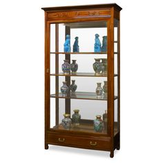 Rosewood Grand Curio Cabinet. With built-in halogen lights projecting museum quality display lighting, our beautiful curio cabinet is perfect for your treasured collectables. Five adjustable shelves and mirrored back inside. One drawer at the bottom with Chinese longevity emblems are masterfully carved out as drawer-pulls. Made of solid rosewood with traditional joinery technique by artisans in China. Hand applied beautiful natural rosewood finish. Curio display cabinet.