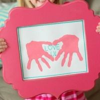A pink picture frame surrounding handprint art