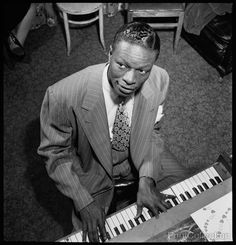 Photo of Nat King Cole playing the piano at a New York City club. Photographed on assignment by William Gottlieb in June of 1947.