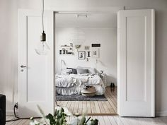 Swedish bedroom with a small gallery wall and crinkled sheets