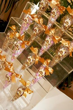Riquísimos cacahuates y deliciosas almendras de chocolate confitadas, todas ellas colocadas en conos de papel y decoradas con un hermoso lazo de cinta francesa en tonalidad ocre, lucen aun más colocadas en esa base de acrílico, desde Feztiva.com