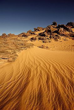 Desert, contrast between rough and smooth show with the rocks and sand
