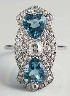 "Art Deco ring , entirely platinum marquise shape , a very original and elegant design , combining a diamond in the center cousin size (4.7 x 4.7 mms, about 0.55 carat ) and two aquamarines Heart shape , a very strong blue . Small cut diamonds ""pink "" dress the set of the ring. French work , circa 1930"
