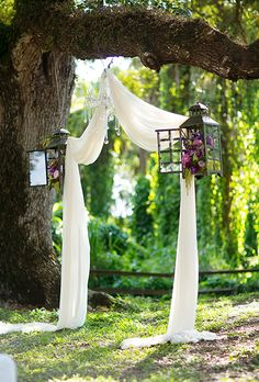 Romantic ceremony space with draped fabric, bookended with flower- and Amaranthus-filled lanterns.