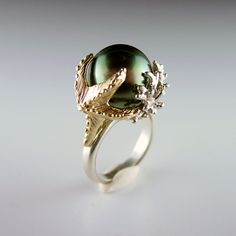 Piece / Title: Starfish & Tahitian Pearl Ring    Keywords: LimitedEdition, Rings, Womens, Cast, Fabricated, HandMade, Pearl    Designer / Author: Dawn Vertrees    Description: This ring features a 13mm Tahitian Pearl set within a beautiful cluster of sculpted coral and a 14K gold starfish. What at way to display an already spectacular pearl!