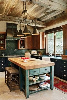 Rustic country kitchen with a wood planked ceiling and exposed beams, a green marble backsplash, and a limestone floor