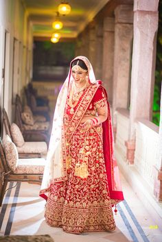 bright red lehenga, gold embroidery, cream dupatta, red scattered motifs, gold kaleere, red and white chooda, smiling bride