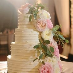 A vine of fresh flowers and a ruffled finish accented the simple four-tiered buttercream cake