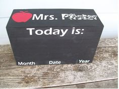 Piece of wood painted with chalkboard paint. Decorated with vinyl - this one was made for a teacher to write the date on but it can be made as a home calendar too :)