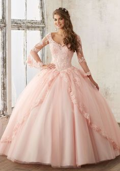 Look Princess perfect in a Mori Lee Valencia Quinceanera Dress Style Number 60015 at your Sweet 15 party. Made out of tulle, this ball gown features feminine bell sleeves, elegant lace details, delica