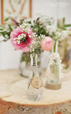 einzelne Blüten in kleinen Vasen mit Anhängern