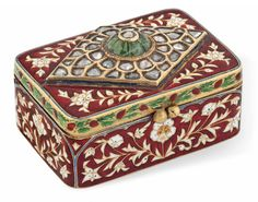 A GEM-SET ENAMELLED GOLD BOX NORTH INDIA, 19TH/20TH CENTURY Of rectangular form, the red enamelled ground decorated with floral arabesques and avian motifs, the lid set with diamonds and a carved emerald, the lid's reverse enamelled with a bird between floral sprays 1¾in. (4.5cm.) across