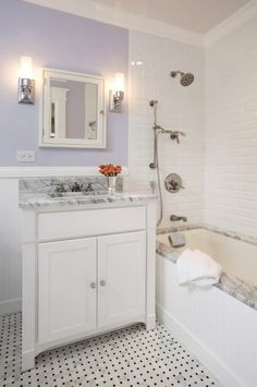 Pretty lilac purple bathroom design with lilac purple walls paint color, white mirror medicine cabinet, Pottery Barn Sussex Tube Sconce, Restoration Hardware Cartwright Powder Room Vanity Sink White with white carrara marble counter top & glass knobs, marble basketweave tiles floor, subway tiles shower surround and polished nickel sconces.